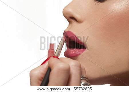 Studio close up over white of an attractive young woman applying her lipstick.