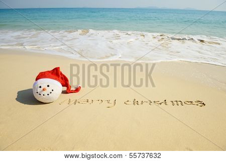 Merry Christmas written on tropical beach white sand with xmas snowman