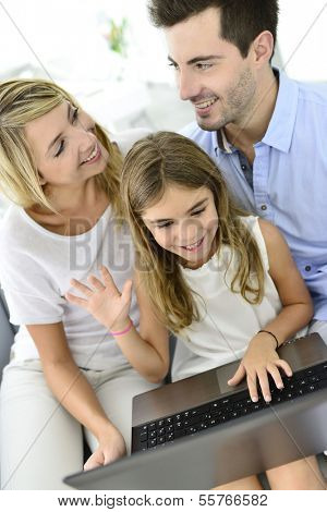 Family having fun chating on internet with laptop