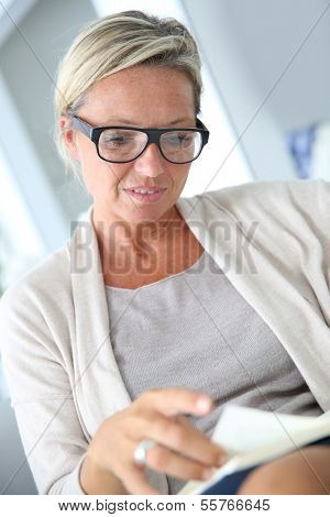 Mature blond woman reading book