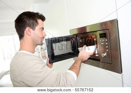 Man heating food in microwave