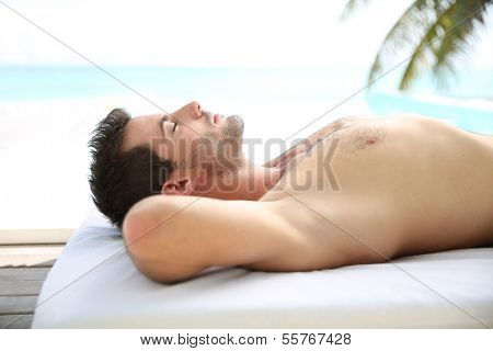 Man relaxing on massage bed outside