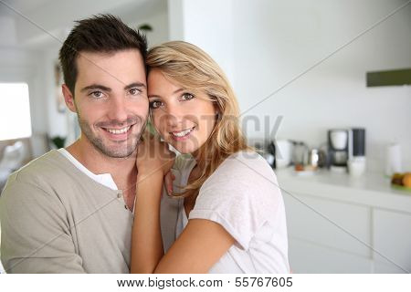 Smiling couple standing in new home ktichen