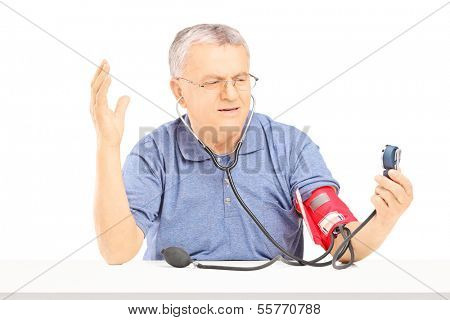 Nervous senior man measuring blood pressure with sphygmomanometer and gesturing with his hand isolated on white background