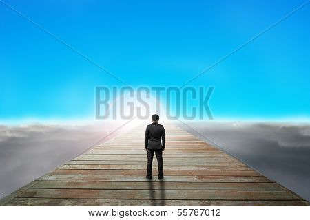 Businessman Standing On Wooden Path Looking Sunrise With Cloudy Below
