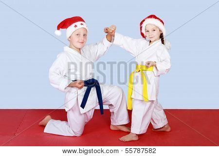 Girl and boy in hats Santa Claus doing hittings and blocks