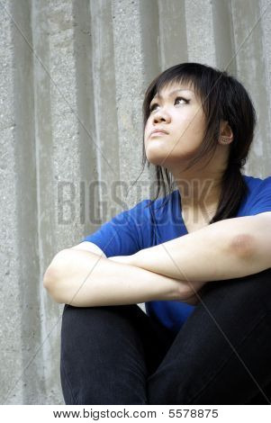 Young asian teen girl seated looking up