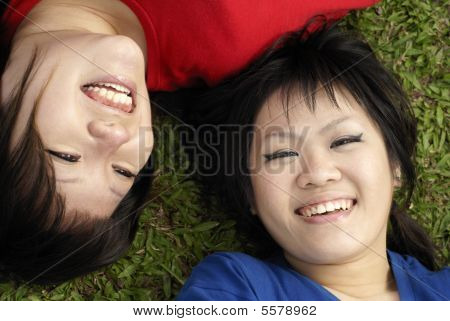 Happy teen girls smiling on grass