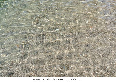 Texture of small pebbles of the sea bottom seen through the water