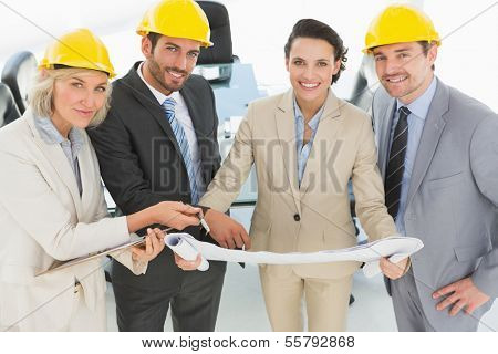 Portrait of well dressed confident architects with hard hats and blueprint standing in the office