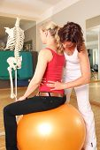 stock photo of spine  - Physiotherapist with patient on gymnastic ball with hands on spine - JPG