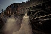 stock photo of locomotive  - Ghost standing by a old locomotive in the dark - JPG
