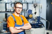 stock photo of manufacturing  - Portrait of young adult experienced industrial worker over industry machinery production line manufacturing workshop - JPG