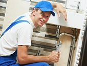 Young happy plumber worker with spanner at sanitary washbasin installation system