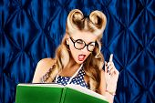 Beautiful pin-up woman with retro hairstyle and make-up posing with a book.