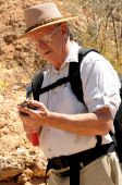 image of paleontologist  - Senior geologist tap a rock formation with a hammer - JPG