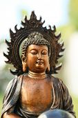 foto of garden sculpture  - Copper like mini sculpture of Buddha on the garden background - JPG