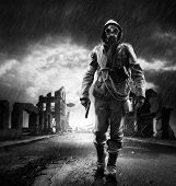 stock photo of gases  - A lonely hero wearing gas mask walking through a city destroyed - JPG