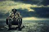 stock photo of rubber mask  - A lonely hero wearing gas mask sitting on armchair - JPG