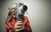 stock photo of nerd glasses  - Nerdy woman using old fashioned cine camera - JPG