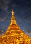 stock photo of yangon  - The shiny golden Shwedagon Pagoda at dusk 6s long exposure with blurred clouds in the night sky Yangon Myanmar Southeast Asia - JPG