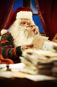 stock photo of letters to santa claus  - Portrait of Santa Claus reading a Christmas letter - JPG
