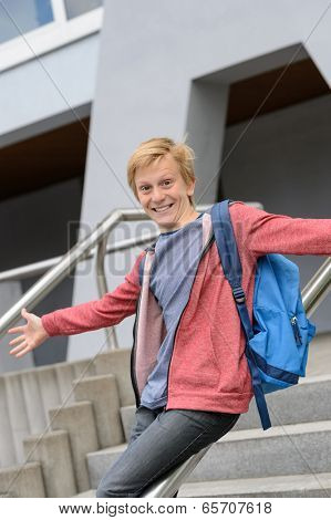 Excited teenage boy sliding down handrail on university stairway