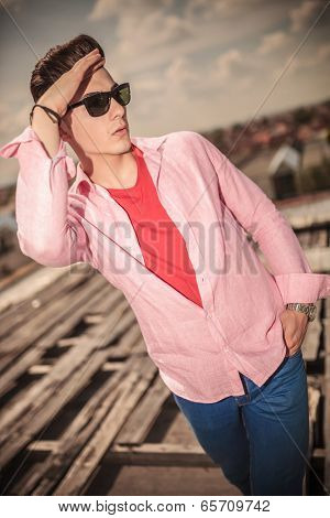 dramatic outdoor picture of a young casual man with hand on his forehead looking far away