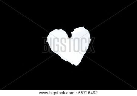 Scrap of white paper in heart shape on black background