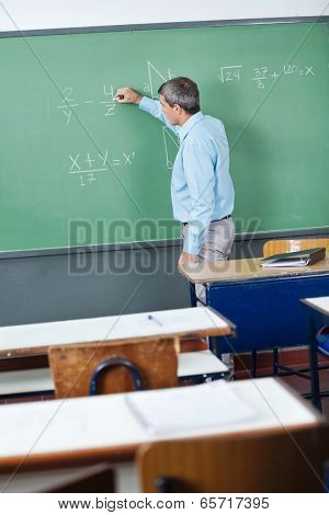 Side view of mature male teacher writing on greenboard in classroom