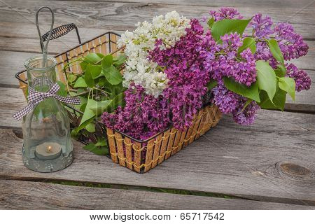 Basket With A Bouquet Of Lilacs And Light With A Burning Candle In The Evening