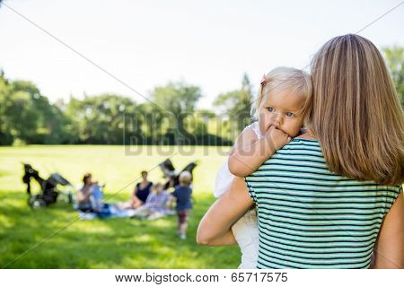 Mother carrying daughter looking away with friends and children in background at park