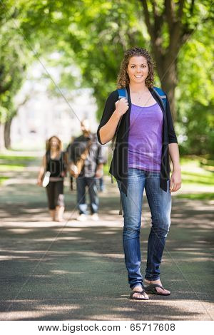 Full length portrait of confident female grad student with backpack standing on campus