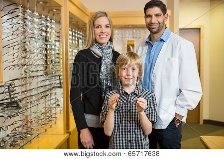 Portrait of boy holding glasses while standing with mother and optician in store