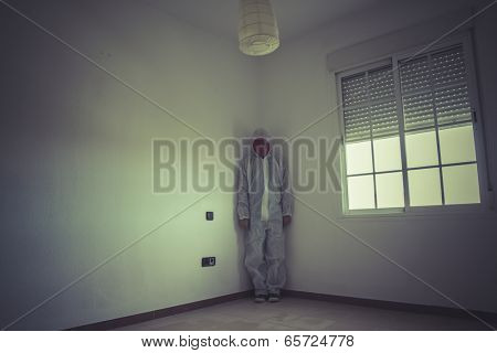 Schizophrenia, nightmare man with red mask in empty room