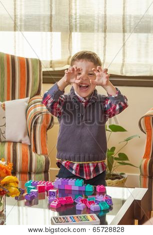 Funny kid making monster face and playing in home