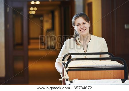 Hotel room service. female housekeeping worker with bedclothes linen in cart