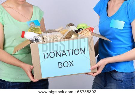 Volunteers with donation box with foodstuffs on grey background