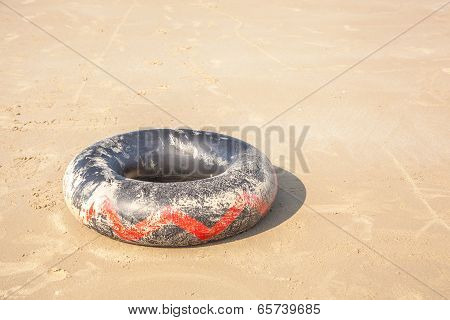 Black Lifebuoy On The Sand