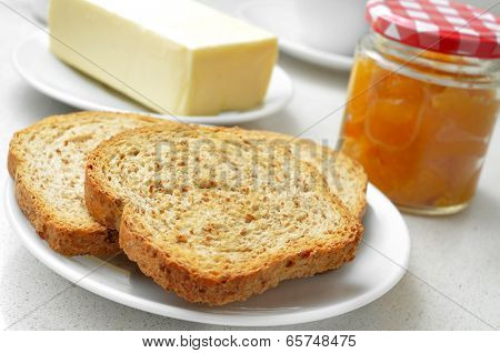a set table with plates with toasts, butter, a jam jar and a cup of coffee in the background