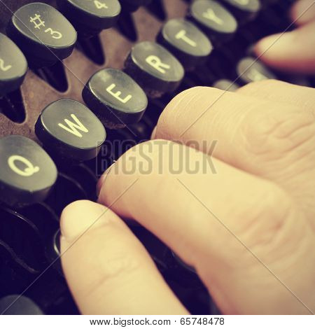 closeup of the hand of a man typing on an old typewriter, with a retro effect