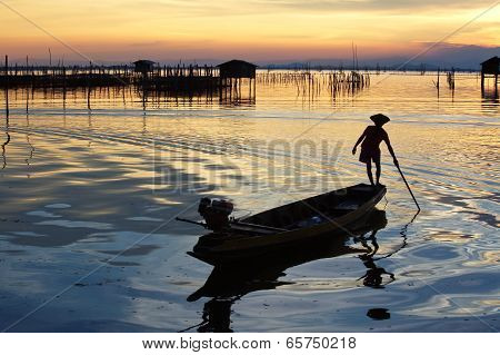 silhouette of fishermen with yellow and orange sun