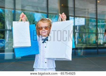 Smiling girl in sunglasses holding shopping bags in hands