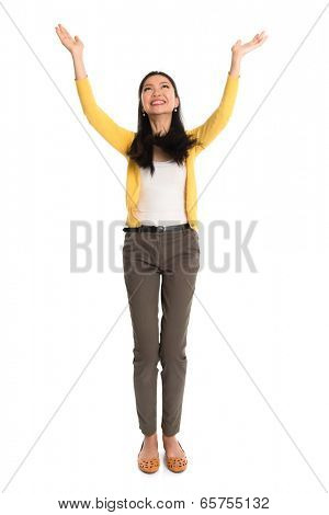 Asian girl arms up, looking upwards like holding something above, full length standing isolated on white background.