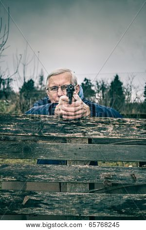 Senior Man Aiming A Gun