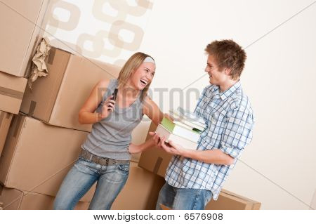 Moving House: Young Couple With Box In New Home