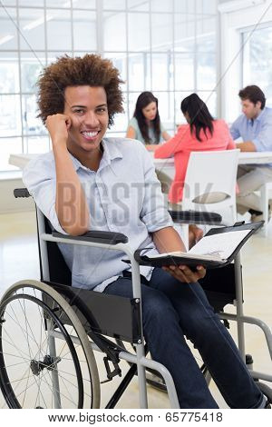 Businessman in wheelchair holding planner and smiling at camera in the office