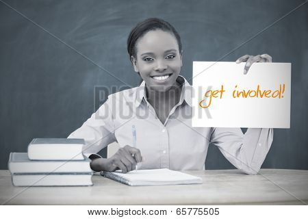 Happy teacher holding page showing get involved in her classroom at school