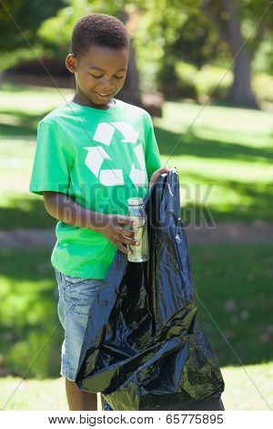 Young boy in recycling tshirt picking up trash on a sunny day