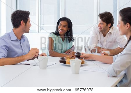 Work colleagues chatting in board room while enjoying coffee and muffins in the office